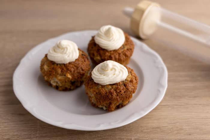 Defrosted stabilized whipped cream piped on 3 muffins