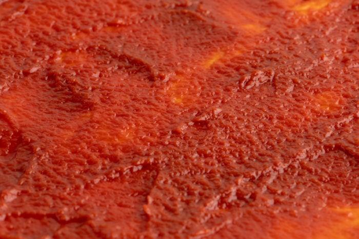 Defrosted tomato paste spread over pizza