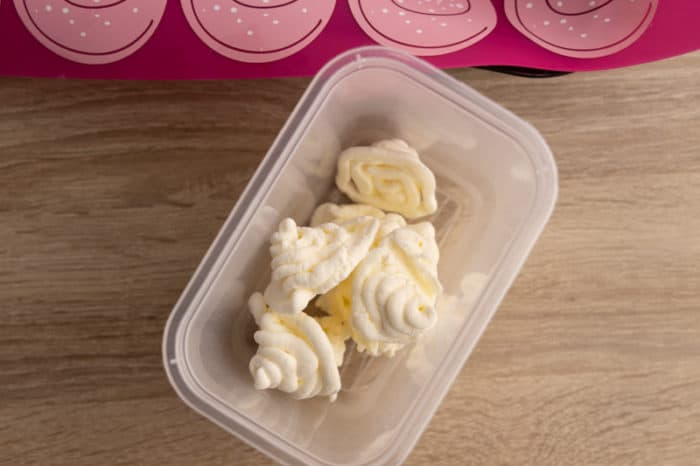 Frozen piped whipped cream transferred into a container