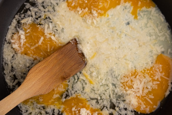 Making scrambled eggs with shredded parm
