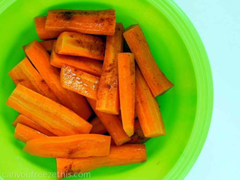 Mixing carrots with olive oil and spices