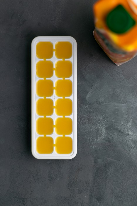 Orange juice poured in an ice cube tray