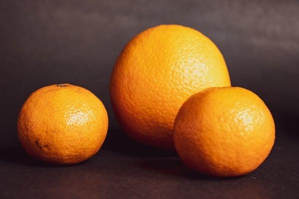 Three oranges on black background